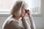 A senior woman pinches the bridge of her nose in discomfort