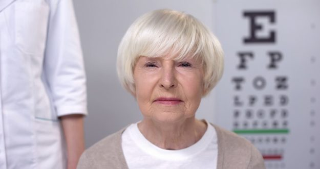 A senior woman stares into the camera. An eye exam chart is out of focus behind her.