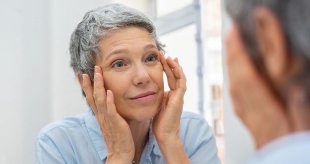 A senior woman touches her temples while looking at herself in the mirror