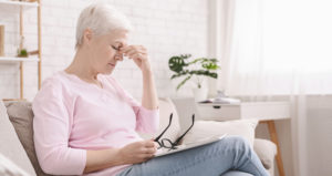 A senior woman holds her glasses on her lap and pinches the bridge of her nose in discomfort