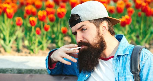A man with a beard squints at the camera and smokes a cigarette