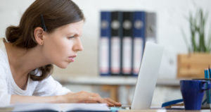 A woman squints her eyes while looking at her laptop screen.