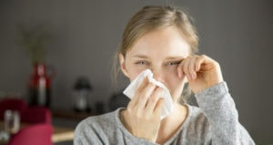 A young woman is crying and wiping her tears away with a tissue and her hand