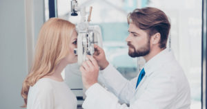 An eye doctor performs an eye exam on a female patient