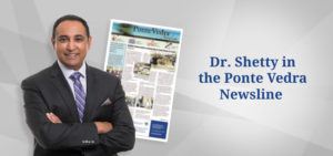"""Dr. Shetty smiles with his arms crossed. An image of the Ponte Vedra Newsline is behind him. Text to his right reads """"Dr. Shetty in the Ponte Vedra Newsline"""""""