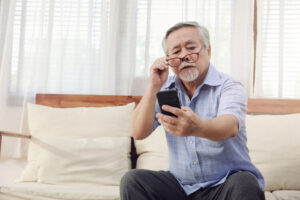 An older man holds his glasses against his face and looks at his phone screen for cataract surgery information