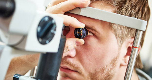 A man is having his eyes examined by a doctor with an eye-exam machine