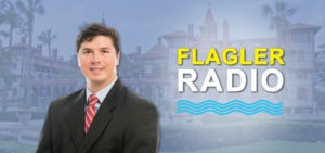 Dr. Koike smiles in front of an image of Flagler College. Flagler Radio logo is featured to the right of him