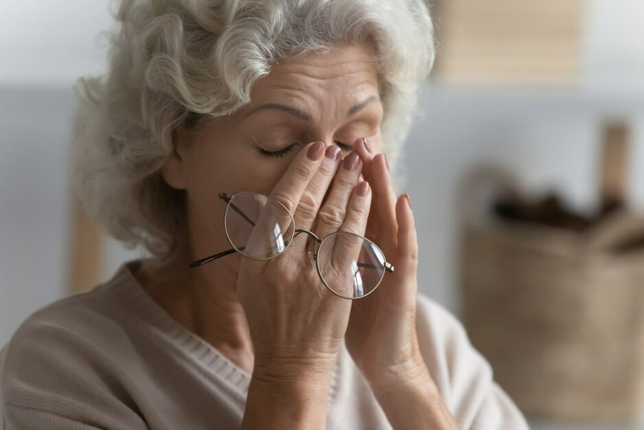 An older woman holds her glasses and rubs her nose and eyes in discomfort, while she deals with vision problems caused by dry eye