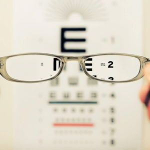 Someone holds a pair of glasses in front of an eye exam chart. The area outside of the glasses is blurry, but the area inside the lenses is clear