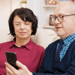 A man wearing glasses and a woman not wearing glasses look at the man's cellphone.