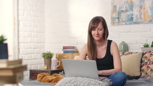 A woman sits on her bed and smiles at her laptop