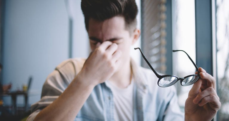A young man is holding his glasses away from his face as he pinches the bridge of his nose in discomfort