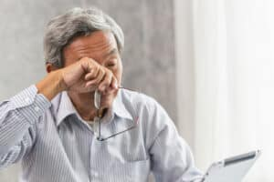 An elderly man holds his glasses and rubs his eyes while trying to read something