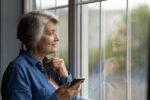 A senior woman looks out the window