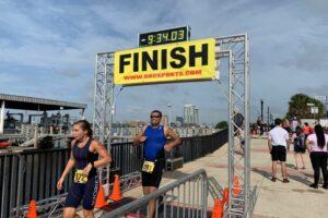 Dr. Ravi Patel runs underneath a race finish line
