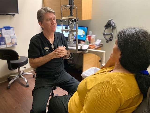 Dr. Kostick talks to a patient sitting in a eye doctor's office