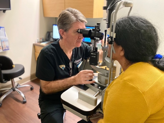 A patient is looking into an eye examining device. Dr. Kostick is looking at the patient's eyes through the device