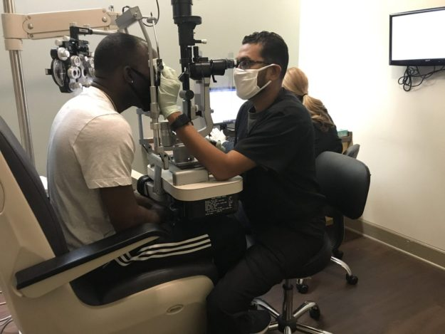 An eye doctor sitting down with patient to examine patients eyes using medical equipment