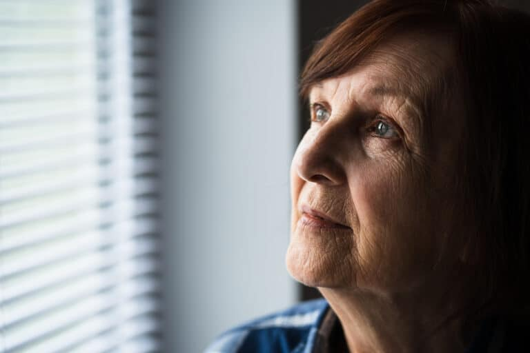 A senior woman looks out her window