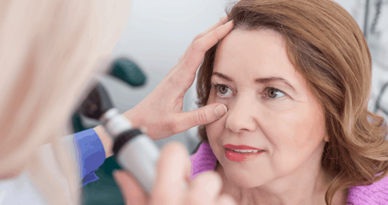 An older woman stares into an eye-examining device. The eye exam is being performed by a blonde eye doctor