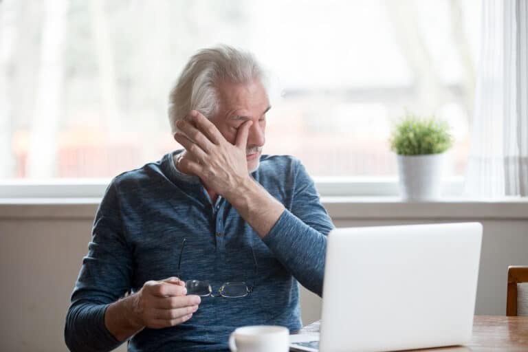 A man holds his glasses and rubs his eyes in discomfort as he uses a computer