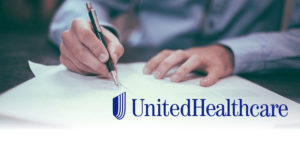 Someone's hands sign a document. The United Healthcare logo is featured at the bottom of the image