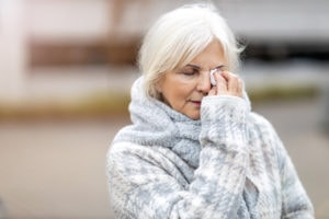 A senior woman wearing a sweater wipes her eyes with a tissue