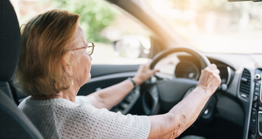 An older woman with glasses is holding her steering wheel while driving