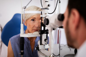 A doctor examines the eyes of a senior woman