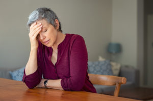 A senior woman holds her head in discomfort