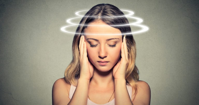 A young woman holds her head and closes her eyes. A graphic of three rings circles around her head indicating the types of ocular migraines