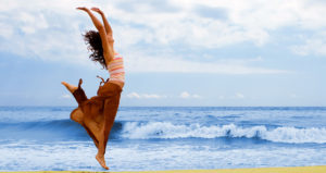 A woman jumps near the shoreline at the beach