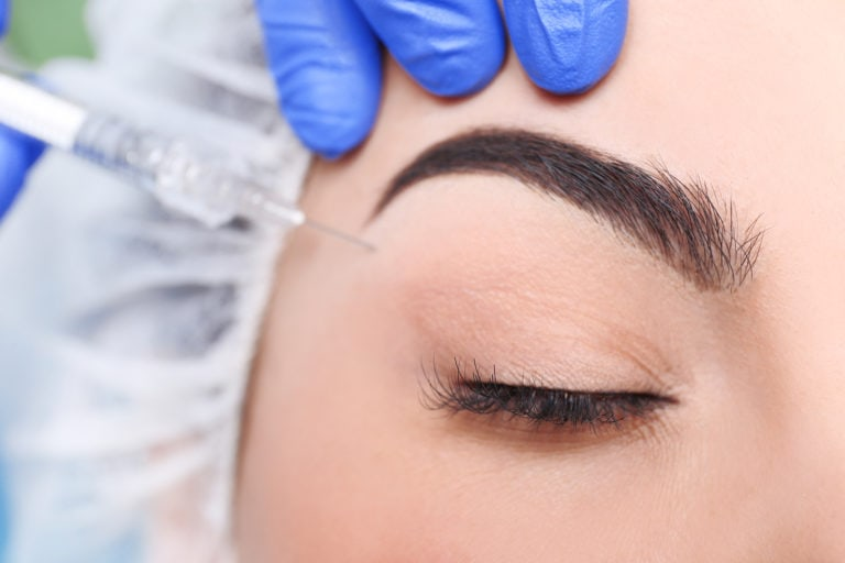 close up of woman getting injection under eye brow, eye closed