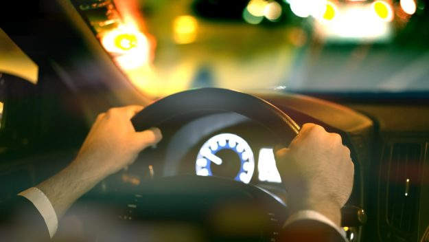 A man's hands grip a car's steering wheel while he faces a blurry road at night.