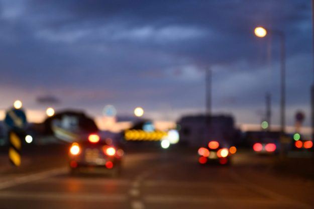Bokeh cars and traffic lights on highway at night