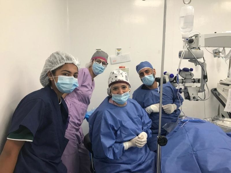 Dr. Chokshi, his daughter and other surgical staff smile in a surgery room