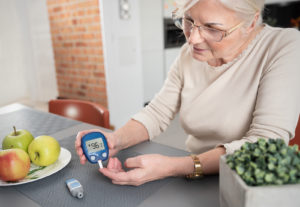 A senior woman checks her blood sugar with glucometer in the kitchen.
