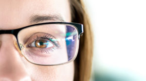A close-up of a woman's brown eyes. She is wearing glasses