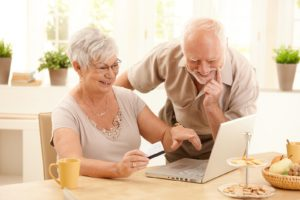 A smiling older couple is looking at a laptop screen. The woman wears glasses and is holding a credit/debit card.