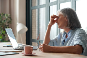 old woman with glasses in hand in front of computer rubbing eyes