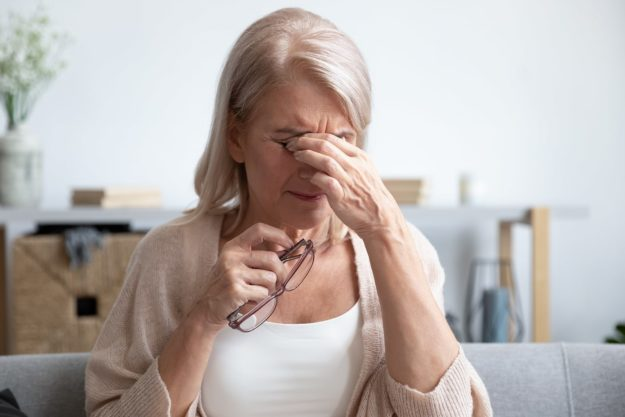 An older woman is pinching her eyes in discomfort. She is holding her glasses in one hand
