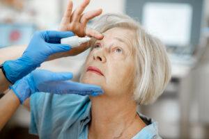 older woman receiving eye drop treatment from nurse