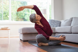 An active, older woman performs stretching exercises on a yoga mat in her living room.